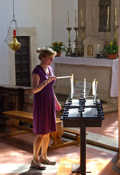 Woman lighting a candle in the Cathedral of Pienza, Siena, Tuscany, Italy