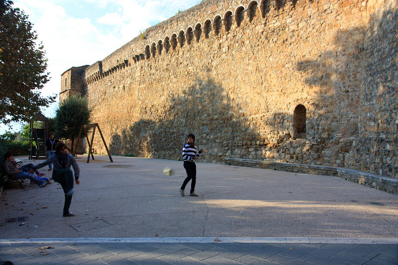 Local kids kicking a soccer ball against the city walls.