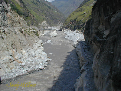 This photo shows the Wangtoo trestle bridge after both the June 2000 and August 2000 floods - the river has changed its mind yet again, and is flowing both under the trestle bridge and to the right of the right bank abutment. The only reason the bridge is still standing at all is that both abutments are founded on solid rock. The right bank roadway, also founded on solid rock at the base of the rock face, has had its gravel surface washed away. This photo was taken from the Shatrujeet bridge.
