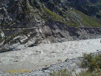 A section of road on the right bank has ceased to exist due to flood damage - a slide has removed an entire portion of the slope. The slope to the left of the slide is so steep that the road is supported by a length of masonry retaining wall.