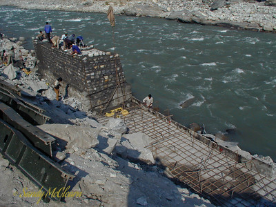 A portion of masonry wall carries on to the left, while formwork and reinforcing steel are prepared for a concrete pour on the right. The masonry wall has mortared masonry on the outside, and loose rubble fill on the inside. This wall will eventually retain the roadway along this side of the river. To the left of the photo are the steel transoms, or joists, that span between the Bailey Bridge trusses and support the roadway, or bridge decking.