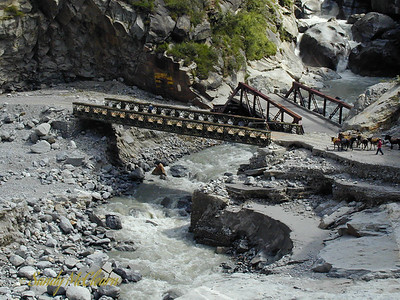 Another view of the small Bailey Bridge on the right bank at Wangtoo. My boss designed the abutments for this bridge, and oversaw its construction. My boss was therefore quite chuffed that the bridge not only survived the June 2000 flood, but also the August 2000 flood. It was therefore somewhat ironic that while this bridge survived the worst that Mother Nature could throw at it, it collapsed several months after this photo was taken when another contractor tried to drive a heavy load over it. The previous bridge, a victim of a flood that occurred before I arrived in India, can be seen in the background.