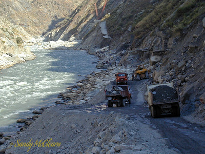 The view looking upstream from the other end, showing the road construction shown in the background of the previous photo. Dump trucks deliver common fill material for the bulldozer in the background to push off. In the background you can see the damaged approach road leading to the upper dam and intakes area, along with the two NCK Rapier crawler cranes in the distance (orange booms).
