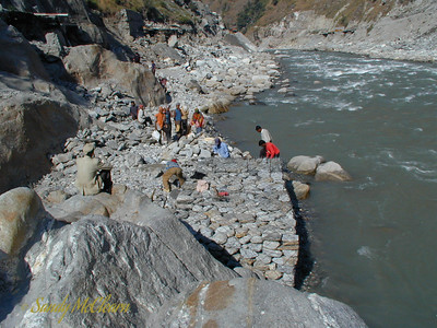 In early October 2000, construction has begun on the road restoration downstream of the Adit 2 bridge abutment. In the foreground, workers fill gabion baskets (galvanized steel wire baskets) by hand with available stone. The baskets will serve as a foundation for masonry retaining walls that will be constructed over the coming months. The foundations in this area will be a mixture of gabions and concrete anchored to bedrock, depending on the area.In the background, heavy equipment is pushing off common fill material to reinstate the road from the downstream end near the workshops.