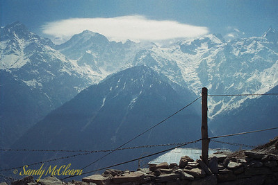 "This photo was taken from the school yard near the top of Reckong Peo, Point ""K"" on the map. One of the peaks visible from this location is Kinner Kailash, a 6050 metre high peak. While not the highest peak in this particular range, I remember it as being the most well known possibly because it was so visible from Reckong Peo, which was the administrative centre for the District of Kinnaur. Most expats ended up travelling here at least once, at it was required for us to check in and get our papers signed by the area Police chief. Behind the camera, local school children sat cross legged on the ground outside of the small school hut learning their lessons."