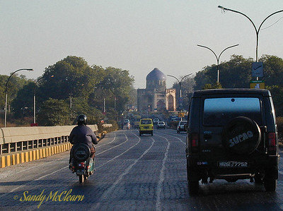 A road in Delhi approaches an abandoned temple. The scooter rider is a bit of a rarity - helmets are not the norm. Note the lack of painted lane lines on the road - even where they exist, motorists tent to ignore them. The mosque in the background is abandoned, except for the pigeons.