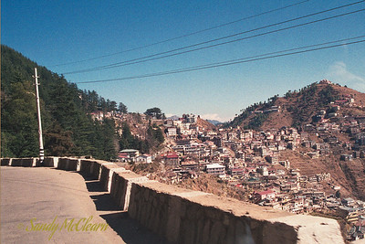 "This is either Shimla (Point ""C"" on the map), or one of the settlements on the outskirts. Shimla is built on the sides and top of a mountain, and it is where the British established there summer capital, so they could escape the stifling heat and humidity of the plains in Delhi."