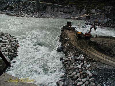 The 1025 dumper drops a load of gravel off the end of the cofferdam, before the dozer heads out to push it off.