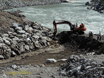 Water rushed through the breach as an excavator works to remove more material.