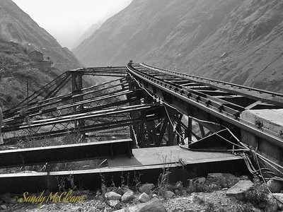 """The following are close-up shots of the cable crane. This crane was built right into the mountain, with one end anchored firmly into the rock high on the right bank, and the other end able to traverse a narrow arc on the track and trestle shown in this photo. This arrangement allowed access to the majority of the dam construction site, although there were some """"dead"""" spots where crawler cranes had to be brought in. The steel trestle shown here was added on later. This photo is looking downstream (to the west)."""