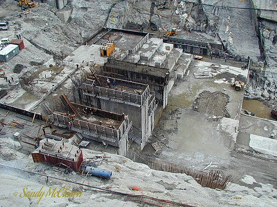 The dam site as seen from the right (north) bank of the Satluj River. The piers of the two nearest sluiceways (Block 8 closest and Block 7 behind) can be seen in the foreground, with the other dam blocks (Block 6 in the middle with Block 5 behind, and Block 4 falling furthest behind in progress) in the background. The river would flow from left to right in this photo. The upstream (left) end of the dam in this photo is the highest part of the dam (now completed), and incorporates the sluice ways and gates. The middle portion of the dam is the spillway bucket, and to the far right is the dam apron which protects the downstream edge of the dam from erosion that could undermine the dam.