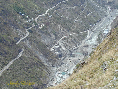 """A closeup of the dam site from further up the mountain. The dam site can be seen at """"F"""" in this map. The main highway to these parts, National Highway (NH) 22 can be seen running along the left (or south) side of the valley wall. The main intakes are also on the south side, with the dam just to the right. The arc of the cable crane track can be seen just up the valley wall from the intakes. A bridge, and some workshops in the distance, can be seen in the upper right of the photo."""