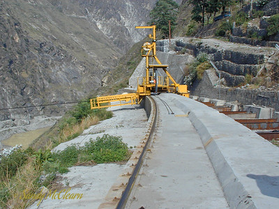 This is the traversing unit of the cable crane. This unit traverses a narrow arc along the combination concrete / trestle track high on the left bank of the dam site. This unit is operated remotely, with the control cab actually installed on the right bank at a much lower elevation, in order to provide better visibility of the dam site. The traversing unit's wheels sit on the steel rail on the front (left) side, and inverted wheels on the back (right) side ride the underside of a second rail which keeps the unit from tipping forward into the valley. To the right, you can see the anchors that keep the whole track from sliding down the mountain. If you look at the satellite photo in Google Maps, you can see the track from space.