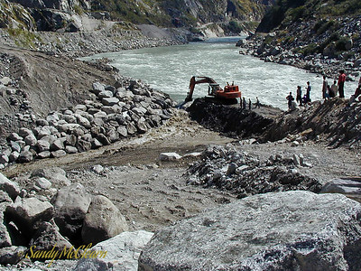 The excavator works to remove more material while more and more water rushes through the gap.