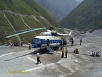 The photographer was never so lucky, but government VIPs got to travel to the dam site by helicopter like the one shown here. The dam site is behind the bend in the river in the background.