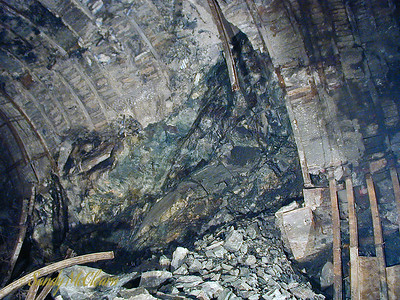 This view is to the right and slightly up from the previous photo - the curved rib in the bottom left can be located in the previous image also. This photo clearly shows the framework of supporting steel ribs with concrete lagging in between. Concrete lagging was pre-cast outside of the tunnel, and each lagging (measuring say 6 inches in width and 2-3 feet in length) would have been installed individually between the channels in each side of the ribs.