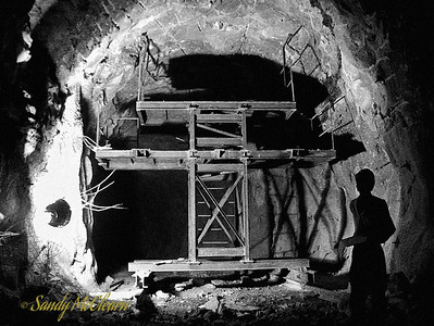 A worker looks at a profiling platform in Outlet Tunnel #2. Once the mass tunnel excavation was finished, a work platform such as this would be run through the tunnel on rails to determine where the rock line was intruding into the tunnel profile, and workers could have go at removing the protuberances with pneumatic hammers. This platform was also fitted with a steel tunnel profile that marked the minimum excavation line, but for some reason that item is not visible here - perhaps this was taken just as the platform was being assembled.