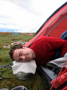 Alex had a long day driving to the festival, and found that our Trangia stove made a comfortable pillow. Nice and warm.
