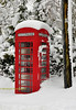 Old red telephone box in the snow