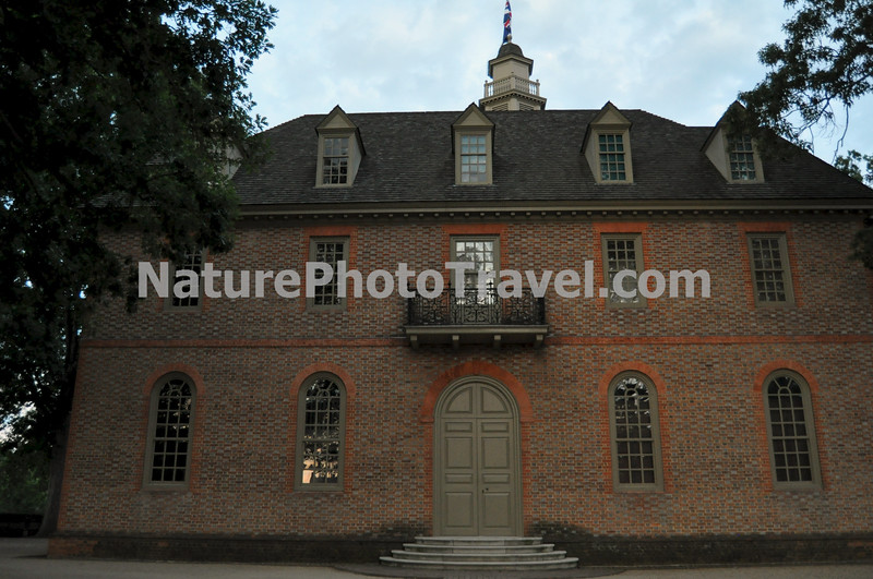 """Colonial Williamsburg: Capitol (Side View): After fire destroyed (for the third time) the Jamestown Statehouse in 1698, the burgesses decided to move the colony's government to Middle Plantation, soon renamed Williamsburg. On May 18, 1699, they resolved to build the first American structure to which the word """"Capitol"""" was applied. A two-story H-shaped structure – really two buildings connected by an arcade was designed. <br /> <br /> The first floor of the west building was for the General Court and the colony's secretary, the first floor of the east part of the building was for the House of Burgesses and its clerk. Arched windows marched across the facades. <br /> Stairs on one side led to the Council Chamber, a lobby, and the Council clerk's office; stairs on the other side led to three committee rooms. A second-floor conference room connected the classically corniced structures."""