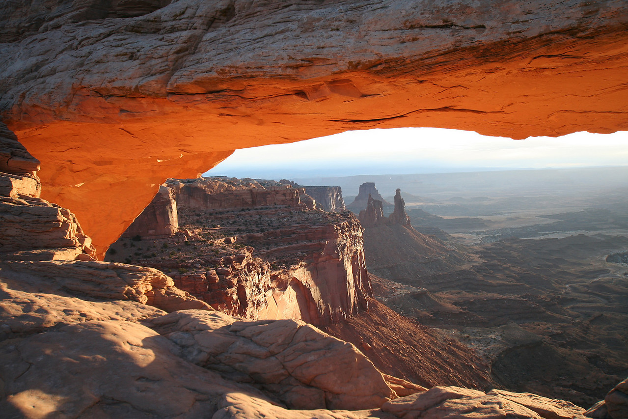 Overlook of Dead Horse Point from Mesa Arch in Canyonland National Park. The arch glows for a few seconds at sunrise, when the sun reflects against the cliff below the arch.
