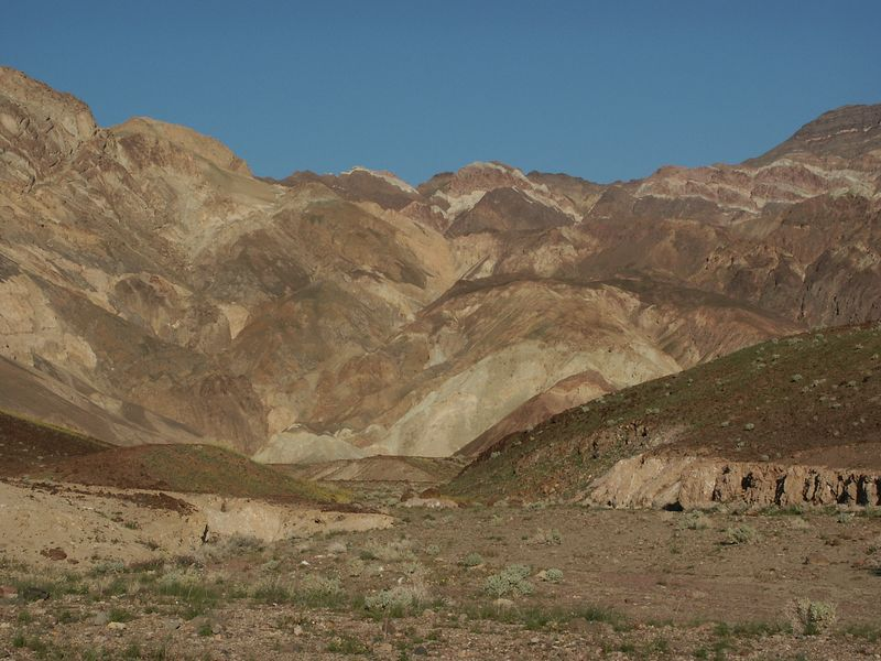 The face of the Black Mountains along Artist's Drive is made up of the multicolored rock of the Artist Drive Formation. Aprons of pink, green, purple, brown, and black rock debris drape across the mountain front, providing some of the most scenic evidence of one of Death Valley's most violently explosive volcanic periods.