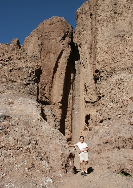 Judy in front of smooth vertical chutes, formed by flood waters flowing from hanging side canyons.
