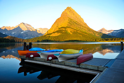 Colorful boats in front of a golden Mount Grinnell.
