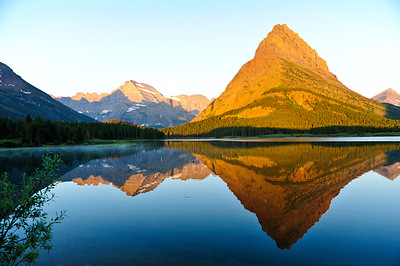 At sunrise Mount Grinnell casts a beautiful reflection in Swiftcurrent Lake.