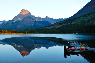 The sun is rising over Swiftcurrent Lake and Mount Wilbur.