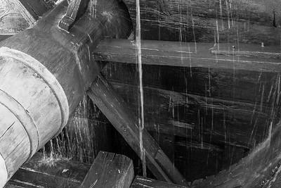Waterwheel shaft driving the bellows inside.