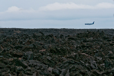Plane landing at Kona Airport.  Looking out over barren field of lava from an 1801 eruption.