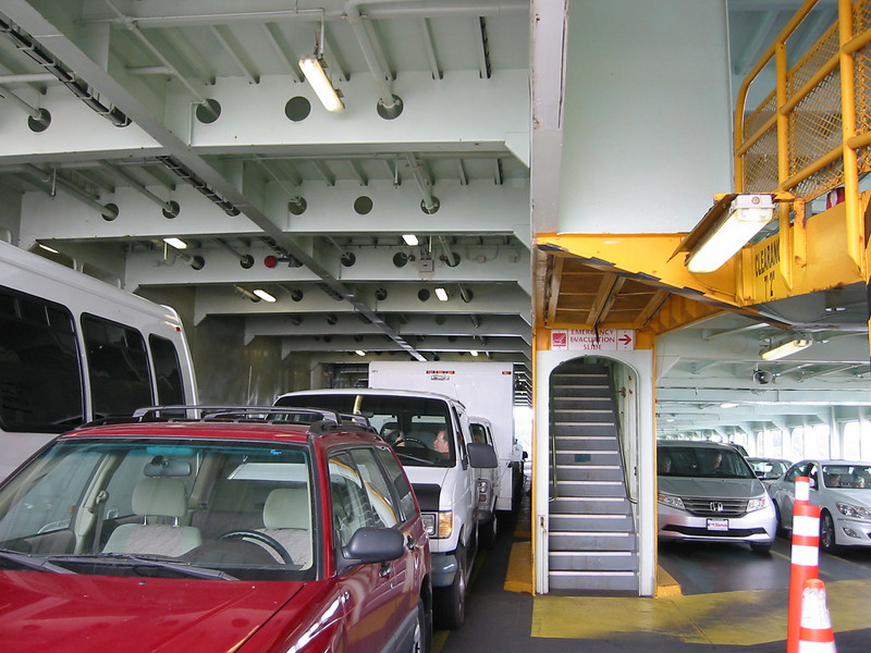 "Back in the main car deck.  To the left of the picture is the center area which has three lines of cars.  To the right is one of the side bays which has two lines of cars.  Above the side bays are the upper car decks which also have two lines of cars each.  The stairs in the middle go up to the upper car deck, then farther up to the passenger deck.<br /> <br /> The red car is my ""Wapple,"" so named because it's red and shiny like a Washington apple.  (Washington State is known for its apples.)  Except when it's brown with dirt, then it's a ""rotten Wapple.""  :D  When it's covered with snow, then it's a ""frosted Wapple."" (See frosted Wapple in 3D here: <a href=""http://www.3dphoto.net/forum/index.php/topic"">http://www.3dphoto.net/forum/index.php/topic</a>,6589.0.html )"