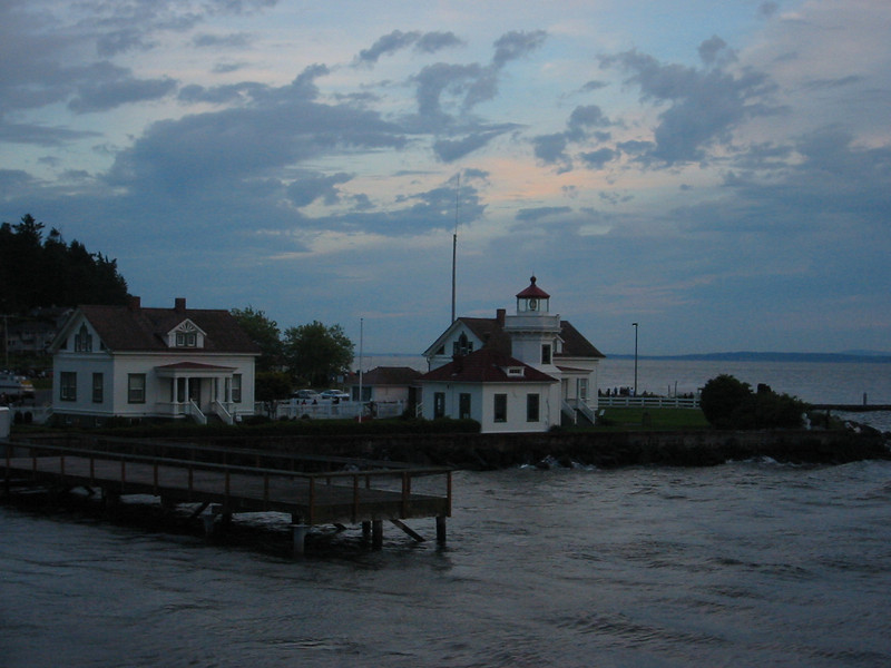 Taken at sunset, the Mukilteo lighthouse, viewed from the upper deck of the ferry going back to Clinton.  The house at the left is where the lighthouse keeper used to live.  I think it's now a gift shop.<br /> <br /> Farther behind the lighthouse (opposite of the ferry) is a small park, a boat launch, and a small pebbly beach.
