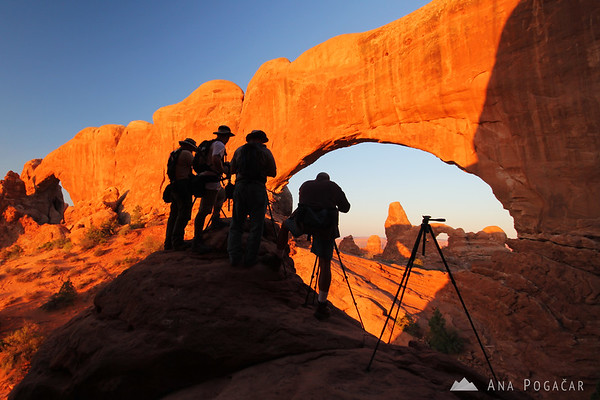 Photographers taking photos of the Turret Arch through the North Window Arch at sunrise, Arches NP