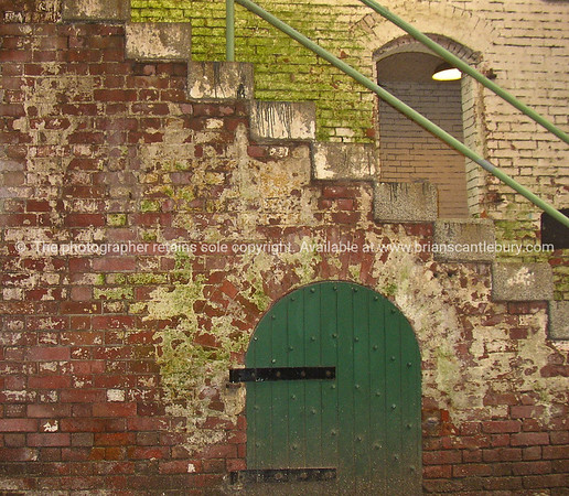 Brick structure, stairs over green door. Alcatraz prison, USA.