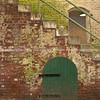 Brick structure, stairs over green door. Alcatraz prison, USA.