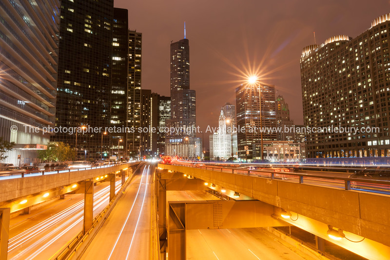 Chicago buildings, towering overhead, overground railway, urban roads, Columbus Drive Bridge and street lights streams with light flares from street lights, Illinois, USA. Looking from th east side to North and the highrise apartments, hotels and commercial buildings.