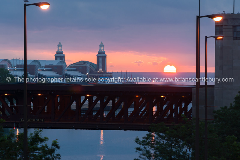 Chicago River Outer Drive double decker bridge sihouetted by distant setting sun across Lake Michigan with Navy Pier between bridge and lake