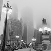 Chicago street as mist descends and lights come on Upper Wacker Drive with ornate lights tall buildings rising into fog.