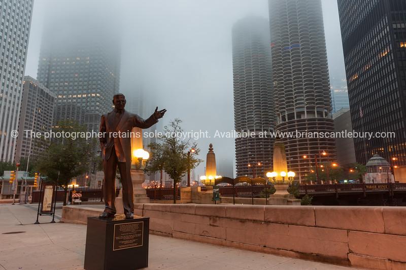 Statue of Mr. Chicago on city riverwalk on misty evening.
