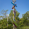 Pole with Route 66 highway shield at top and place names below on colored signs.