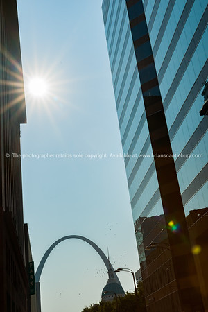 St Louis Gateway Arch at end of city street framed by high-rise buildings with sunburst. St Louis, architecture, and famous arch, Missouri,USA.