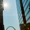 St Louis Gateway Arch at end of city street framed by high-rise buildings with sunburst.