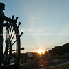 Bronze public art statue in Glascock's Landing looking over Mississippi River commemorates Mark Twain's training as steamboat pilot silhouette in setting sun Hannibal Missouri USA historic hometown of Mark Twain.