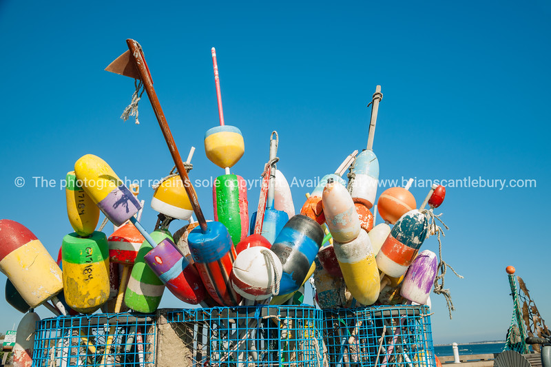 Collection of colorful fishing or lobster trap buoys and markers at wharf in Provincetown, Massachusetts, USA