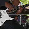 Guitarist plucking base guitar, close up, drummer in background. Playing for the crowd outdoors in New Orleans.