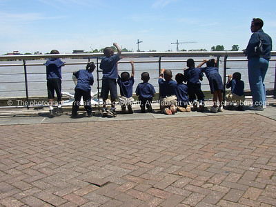 Children and teacher, in uniform at edge of Mississippi River, New Orleans.