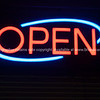 Neon Open sign against black background.