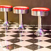 Black and checcker floor pattern, chrome stools with red vinyl seats